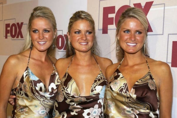 Jaclyn, Erica, and Nicole, a set of identical triplets, wearing matching dresses with matching hairstyles on the red carpet
