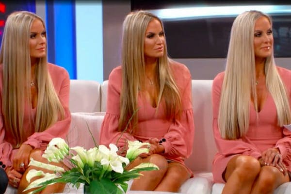 Jaclyn, Erica, and Nicole sat on a sofa wearing matching coral dresses with their long, blonde hair worn straight down