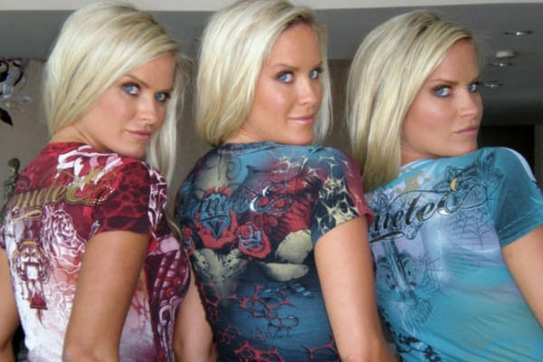 Jaclyn, Erica, and Nicole all wearing graphic t-shirts standing away from the camera while looking back and smiling over their shoulders