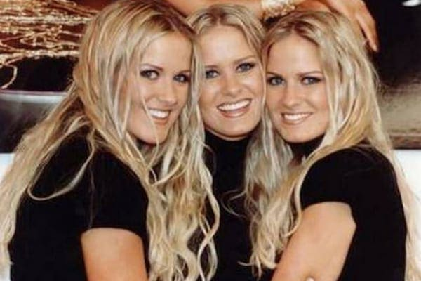 Jaclyn, Erica, and Nicole with curly blonde hair wearing black turtleneck sweaters hugging each other