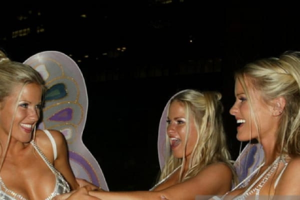 Jaclyn, Erica, and Nicole wearing bikinis and fairy wings with their hair tied back laughing and joking with each other