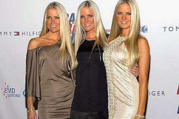 Jaclyn, Erica, and Nicole wearing three different dresses with their arms around each other on the red carpet