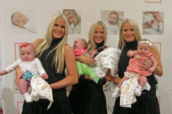 Jaclyn, Erica, and Nicole wearing matching black dresses while holding their baby daughters behind the scenes of The Doctors