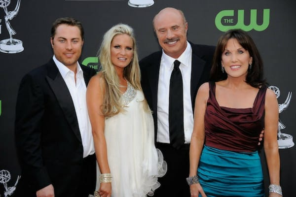 Erica and Jay McGraw with Dr. Phil and his wife, Robin McGraw, posing together on the red carpet