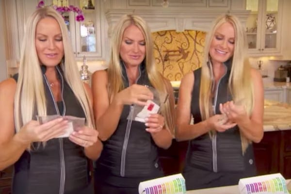 Jaclyn, Erica, and Nicole wearing matching zipped vests holding their DNA testing kits on The Doctors