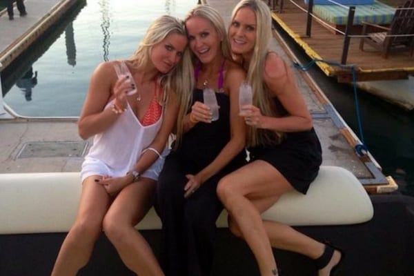 Jaclyn, Erica, and Nicole sitting on the seat of a boat at the edge of the water toasting with a glass
