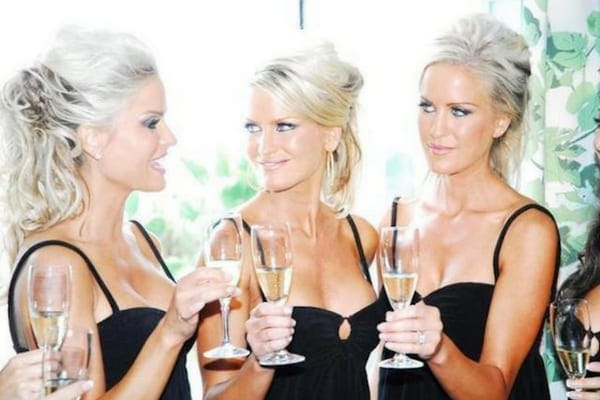 Jaclyn, Erica, and Nicole all toasting champagne together while wearing matching black ball gowns