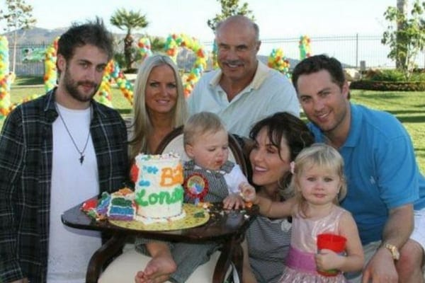 Family photo of Erica and Jay McGraw with Robin and Dr. Phil, and the children Avery and London at a children's birthday party