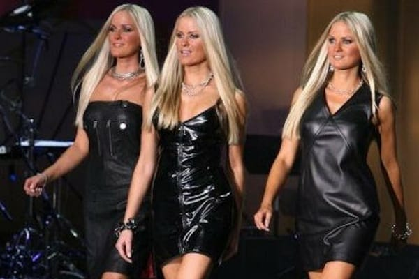 Jaclyn, Erica, and Nicole wearing black leather dresses on the catwalk with their long blonde hair worn straight down