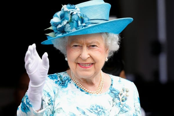 Queen Elizabeth II waving to the crowd while wearing a blue floral outfit with a matching blue hat finished with flowers
