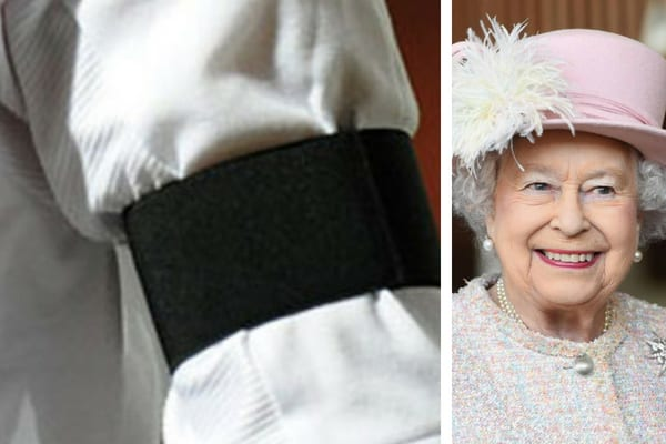 A person wearing a white shirt with a black armband around their left arm, and Queen Elizabeth II smiling