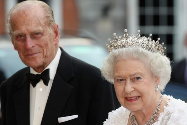 Queen Elizabeth II wearing one of her crowns and matching necklaces walking with Prince Philip dressed in a suit and bow tie