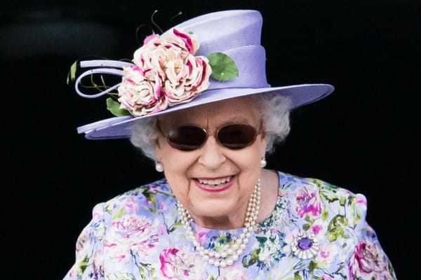 Queen Elizabeth II wearing a matching purple floral outfit and hat with a pair of dark, round sunglasses
