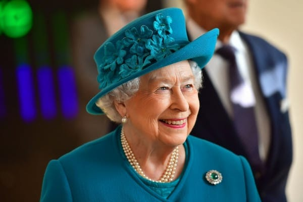 Queen Elizabeth II smiling off to one side wearing a sea blue matching jacket and floral hat with a brooch