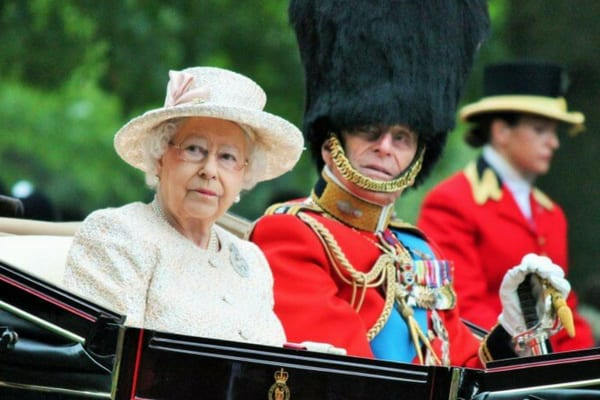 Queen Elizabeth II wearing her glasses next to Prince Philip wearing a bearskin hat in the back of a carriage