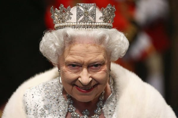 Queen Elizabeth II wearing one of her crowns with a silver jeweled outfit and a fur shrug on her shoulders