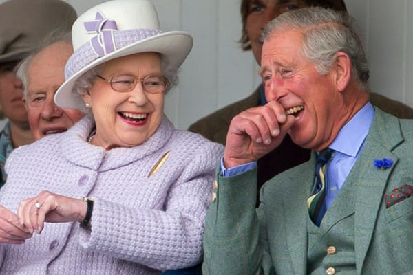 Queen Elizabeth II wearing a purple coat with a matching hat sat next to Prince Charles laughing in a tweed suit