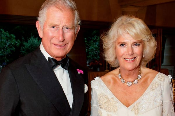 Prince Charles wearing a suit and bow tie standing with his wife, Camilla, wearing a white and gold gown