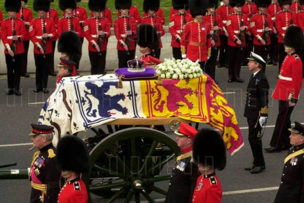 The Queen's Mother's coffin as it is led through London by the guards with her crown on a purple pillow on top of the coffin
