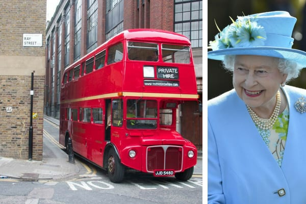 Red London bus on a side road in the city, and Queen Elizabeth II wearing a light blue jacket and matching hat